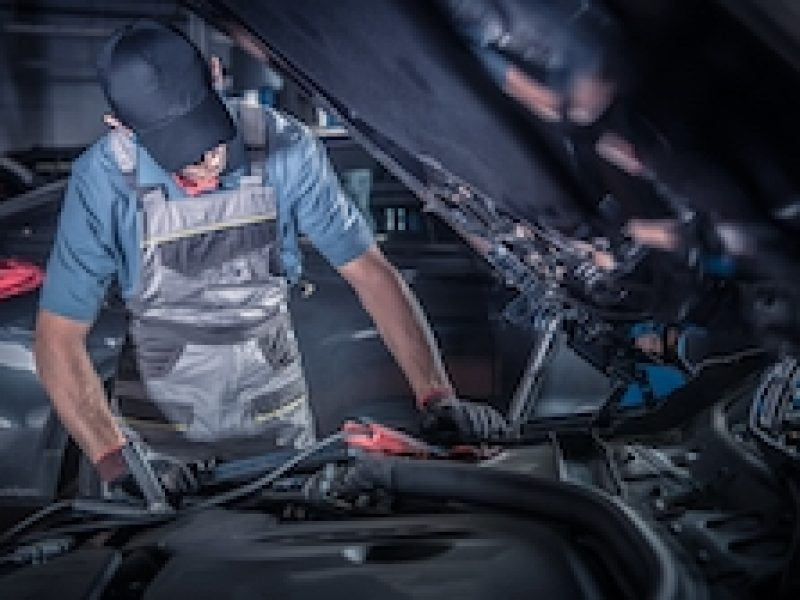 Car Mechanic Work. Caucasian Vehicles Technician Looking Under Car Hood Looking For the Existing Problem. Automotive Industry.