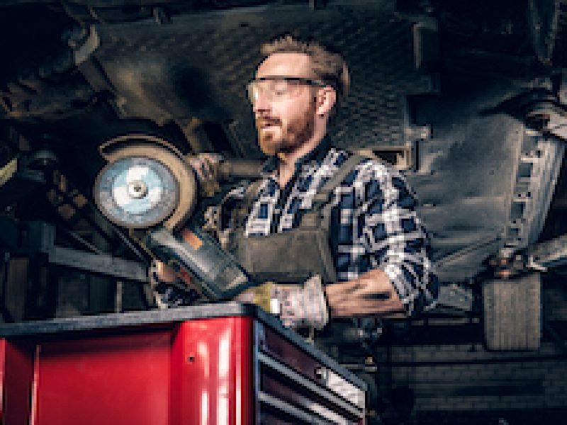Bearded mechanic in protective googles holds angle grinder near the car in a workshop.